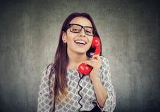 Szczęśliwa atrakcyjna kobieta opowiada na retro telefonie nad ściennym tłem zdjęcie stock