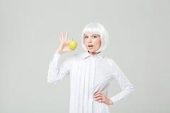 Szczęśliwa atrakcyjna młoda kobieta trzyma świeżego jabłka z blondynka włosy Fotografia Stock