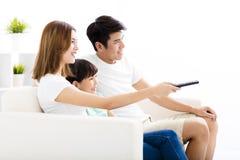 Szczęśliwa Atrakcyjna Młoda rodzina ogląda tv zdjęcie royalty free