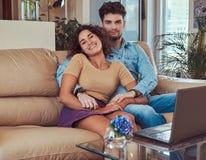 Szczęśliwa atrakcyjna para podczas weekendu, ogląda film na laptopu obsiadaniu na kanapie w domu zdjęcie royalty free
