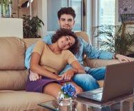 Szczęśliwa atrakcyjna para podczas weekendu, ogląda film na laptopu obsiadaniu na kanapie w domu obraz stock