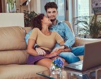 Szczęśliwa atrakcyjna para podczas weekendu, ogląda film na laptopu obsiadaniu na kanapie w domu obrazy royalty free