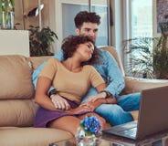 Szczęśliwa atrakcyjna para podczas weekendu, ogląda film na laptopu obsiadaniu na kanapie w domu zdjęcie stock