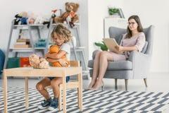 Szczęśliwa autystyczna chłopiec bawić się z pluszową zabawką i jego psychologiem obrazy stock