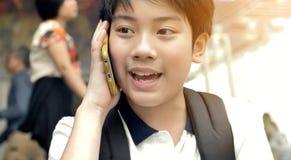 Szczęśliwa Azjatycka chłopiec opowiada z telefonem komórkowym z uśmiech twarzą zdjęcia royalty free