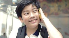 Szczęśliwa Azjatycka chłopiec opowiada z telefonem komórkowym z uśmiech twarzą fotografia stock