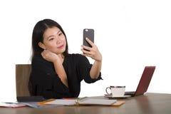 Szczęśliwa Azjatycka Chińska biznesowa kobieta bierze selfie fotografię z telefonem komórkowym przy korporacyjny firmy biurowego  zdjęcia royalty free
