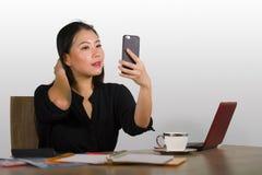 Szczęśliwa Azjatycka Chińska biznesowa kobieta bierze selfie fotografię z telefonem komórkowym przy korporacyjny firmy biurowego  obraz royalty free