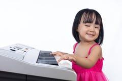 Szczęśliwa Azjatycka Chińska mała dziewczynka bawić się elektryczną fortepianową klawiaturę Fotografia Royalty Free