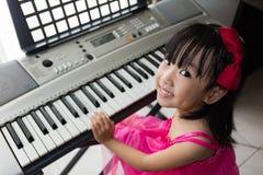 Szczęśliwa Azjatycka Chińska mała dziewczynka bawić się elektryczną fortepianową klawiaturę Zdjęcie Stock