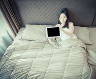 Szczęśliwa Azjatycka kobieta pokazuje pustego ekran pastylka na łóżku Fotografia Royalty Free