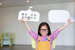 Szczęśliwa Azjatycka mała dziewczynka trzyma w górę papier szkoły w kolorów żółtych dungarees i pusta pusta mowa gulgoczemy mówić fotografia royalty free