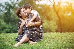 Szczęśliwa Azjatycka rodzina, matka z jej synem przy parkiem obraz stock