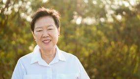 Szczęśliwa Azjatycka starsza kobieta ono uśmiecha się w ranku słońcu z zielenią z powrotem obraz stock