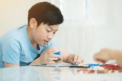 Szczęśliwa azjatykcia chłopiec bawić się klingerytu blok w domu Zdjęcia Stock
