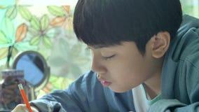 Szczęśliwa azjatykcia chłopiec robi twój pracie domowej z uśmiech twarzą 4K zbiory