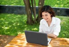 Szczęśliwa azjatykcia dziewczyna śmia się i wskazuje na laptopu ekranie dalej przewyższa Obraz Stock