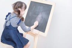 Szczęśliwa azjatykcia dziewczyna dzieciaka remisu kreskówka z kredą na blackboard Zdjęcie Stock