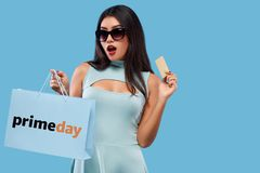 Szczęśliwa azjatykcia kobieta przy zakupy mienia torbą i telefonem odizolowywającymi na błękitnym tle na czarnym Piątku i primeda obraz royalty free