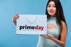 Szczęśliwa azjatykcia kobieta przy zakupy mienia torbą i telefonem odizolowywającymi na błękitnym tle na czarnym Piątku i primeda obrazy stock