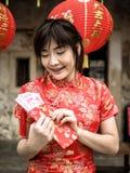 Szczęśliwa azjatykcia kobieta trzyma czerwoną kieszeń z chińczykiem w tradycyjni chińskie sukni sto Juan banknotów szczęsliwych p obrazy stock