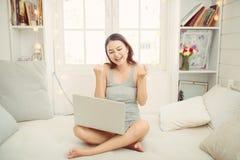 Szcz??liwa azjatykcia kobieta u?ywa laptop w ranku podczas gdy siedz?cy na ? fotografia royalty free