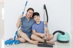 Szczęśliwa azjatykcia rodzina czyści pokój zdjęcie stock