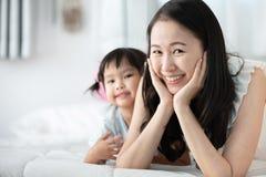 Szczęśliwa azjatykcia rodziny matka z córką bawić się na łóżku z smil zdjęcie stock