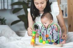 Szczęśliwa azjatykcia rodziny matka z syna dzieckiem bawić się na łóżku z smil obraz royalty free
