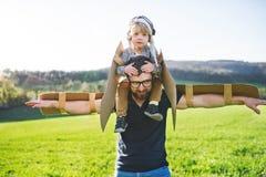 Szczęśliwa berbeć chłopiec, ojciec bawić się z skrzydłami outside w wiosny naturze i zdjęcie stock