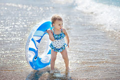 Szczęśliwa berbeć dziewczyna z nadmuchiwanym okręgiem przy morzem zdjęcia royalty free