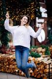 Szczęśliwa biała dziewczyna z długim ciemnym włosy w pulowerze, girlandy w bokeh, wakacyjna wygodna atmosfera, uśmiechnięta kobie obrazy royalty free