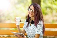 Szczęśliwa biurowa kobieta z kawą i pastylką na parkowym tle Przypadkowy stylu życia pojęcie Zdjęcie Stock