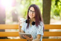 Szczęśliwa biurowa kobieta z kawą i pastylką na parkowym tle Przypadkowy stylu życia pojęcie Obrazy Stock