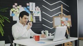 Szczęśliwa biznesmen odzieży słuchawki opowiada patrzejący laptop i pijący kawę zbiory