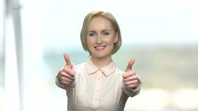 Szczęśliwa biznesowa kobieta daje dwa aprobatom zbiory