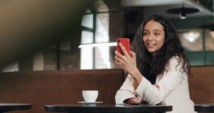 Szczęśliwa biznesowa kobieta opowiada na telefonie ma rozmowę przez wideo gadki konferencji przy wygodną kawiarnią Biznesowej kob zbiory