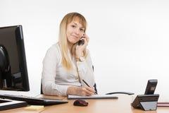 Szczęśliwa biznesowa kobieta opowiada na telefonu komórkowego writing w dzienniczku zdjęcia royalty free
