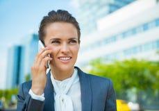 Szczęśliwa biznesowa kobieta opowiada smartphone w biurowym okręgu Fotografia Royalty Free