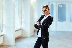 Szczęśliwa biznesowa kobieta patrzeje ufny z nowożytnym budynkiem Obrazy Stock