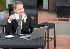 Szczęśliwa biznesowa kobieta relaksuje z filiżanką kawy i patrzeje laptopu ekran obrazy royalty free