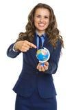 Szczęśliwa biznesowa kobieta wskazuje na ziemskiej kuli ziemskiej Obrazy Royalty Free