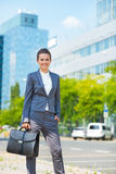Szczęśliwa biznesowa kobieta z teczką w nowożytnym biurowym okręgu Fotografia Royalty Free