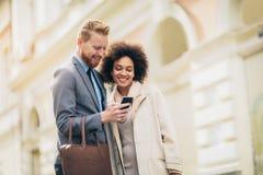 Szczęśliwa biznesowa para używa mądrze telefon fotografia stock