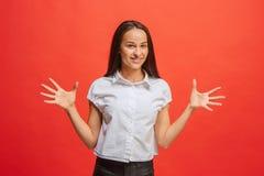 Szczęśliwa biznesowej kobiety pozycja i ono uśmiecha się przeciw czerwonemu tłu Obrazy Stock