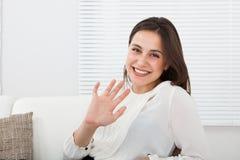 Szczęśliwa bizneswomanu falowania ręka na kanapie fotografia royalty free