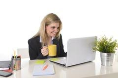 Szczęśliwa blond biznesowa kobieta pracuje na komputerowym laptopie z filiżanką Fotografia Stock