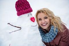 Szczęśliwa blond dziewczyna pozuje blisko postaci robić śnieg fotografia stock