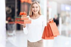 Szczęśliwa blondynka z torba na zakupy i prezentów pudełkami w centrum handlowym obraz royalty free