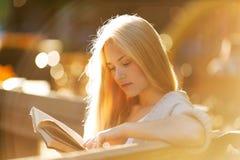 Szczęśliwa blondynki dziewczyna czyta książkę Zdjęcia Royalty Free